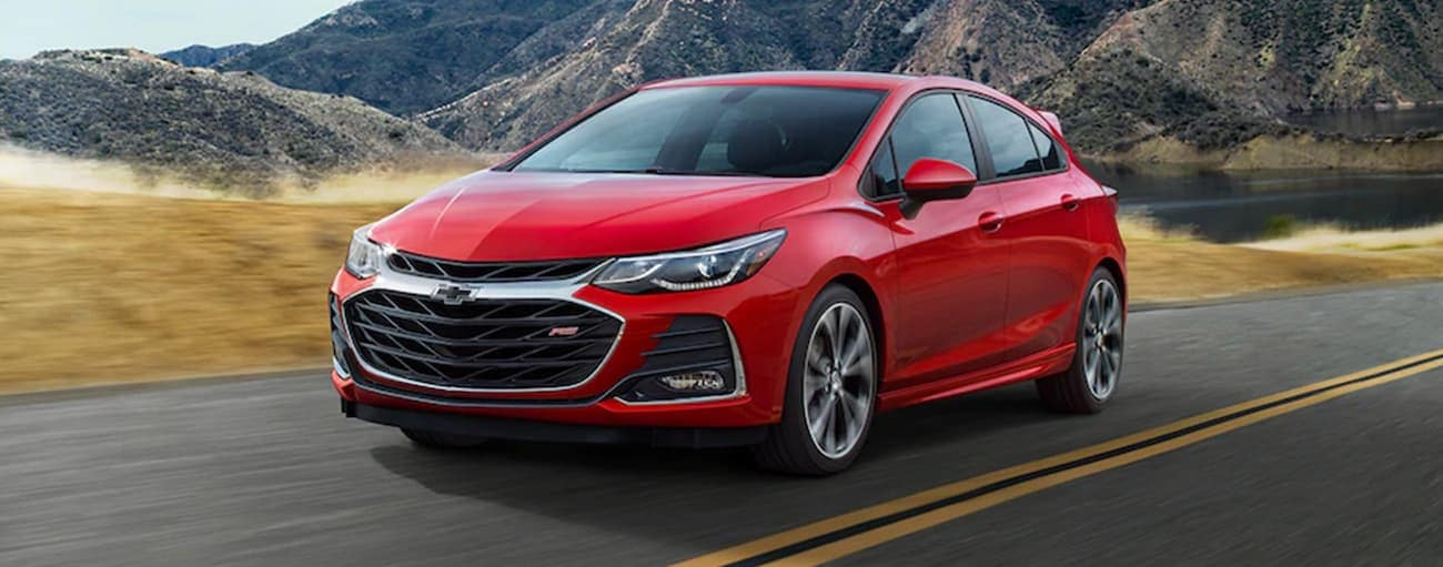 A red 2019 used Chevrolet Cruze is driving away from mountains.