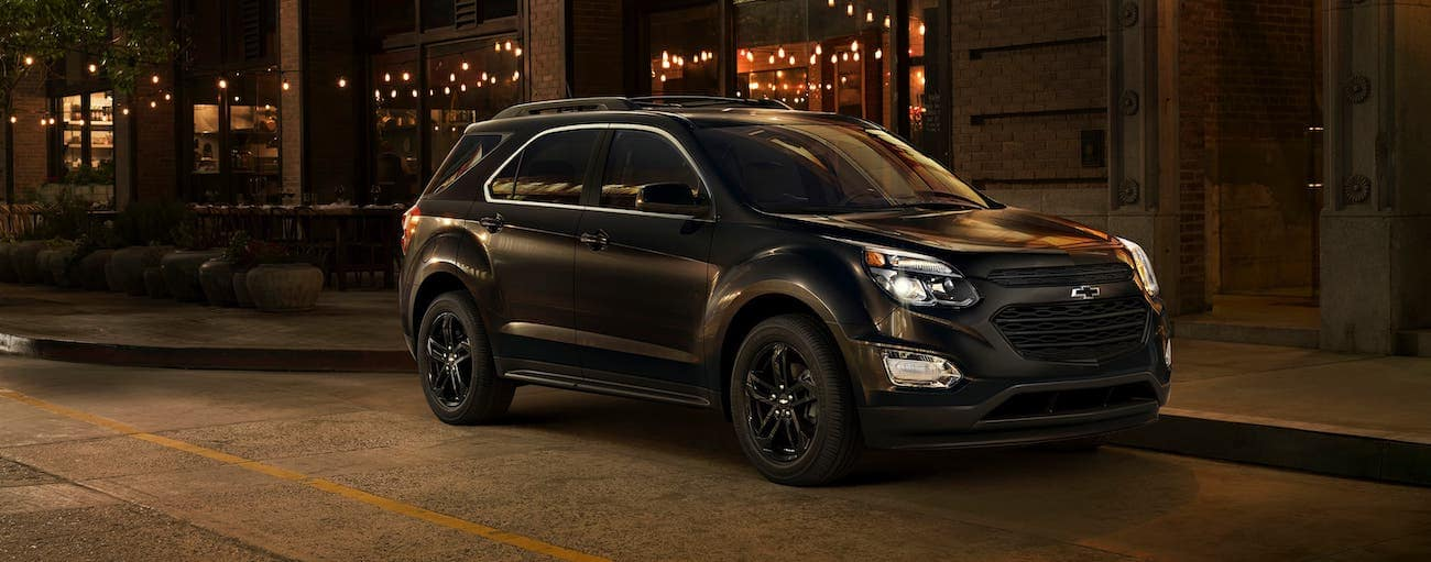 A black 2017 used Chevrolet Equinox Midnight Edition is parked on an Indianapolis, IN, street at night.