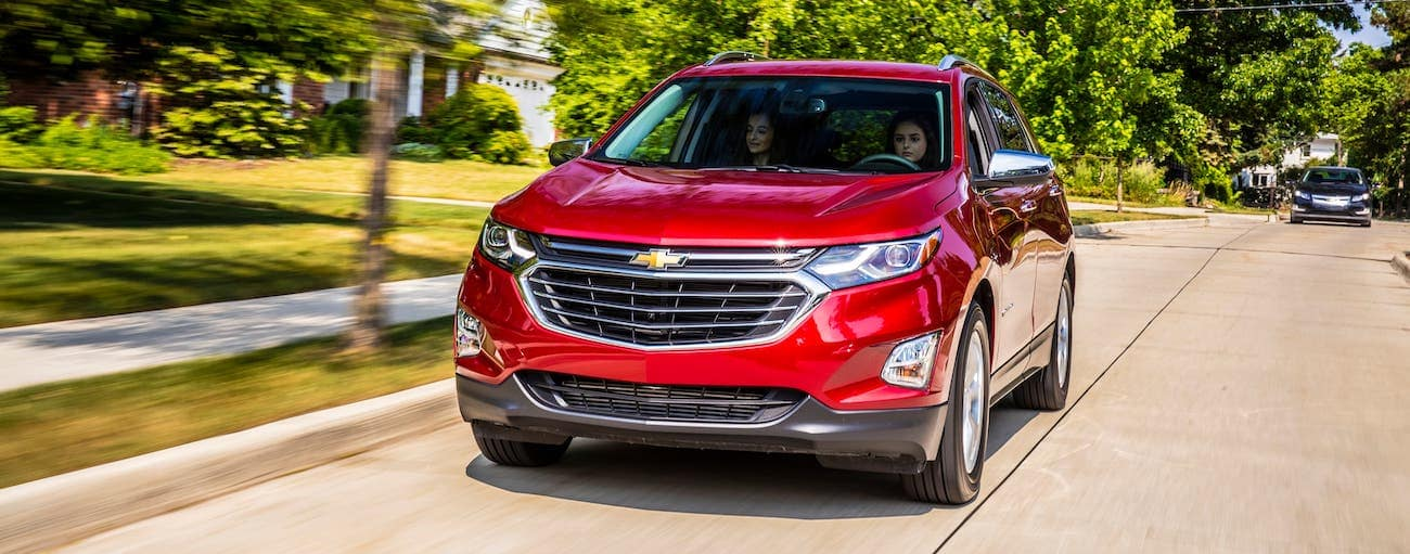 A red 2018 used Chevrolet Equinox is driving on a suburban road.