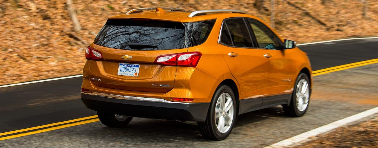 An orange 2019 used Chevrolet Equinox is driving on a rural road in fall.