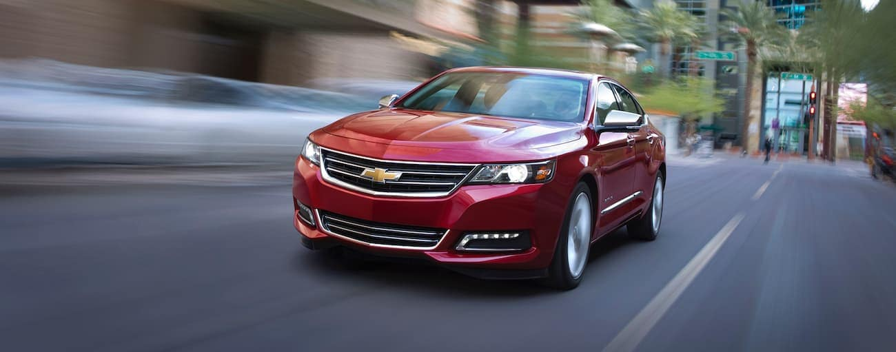 A red 2016 used Chevrolet Impala is driving on a city street near Indianapolis, IN.