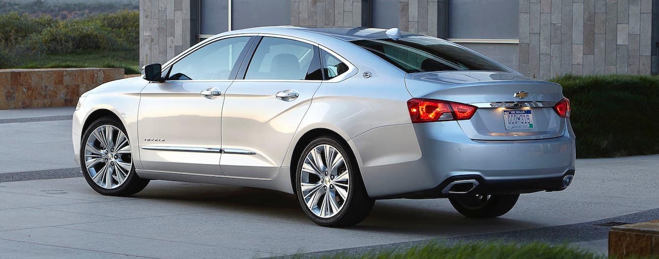 A silver 2017 used Chevrolet Impala is parked outside a modern house.