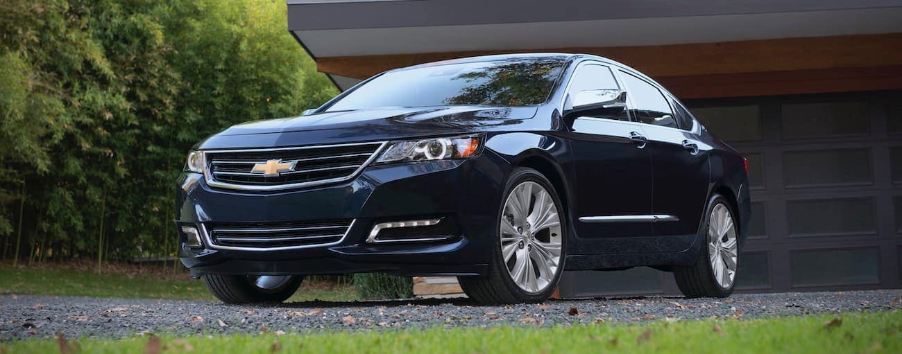 A blue 2018 used Chevrolet Impala is parked in front of a black garage door.