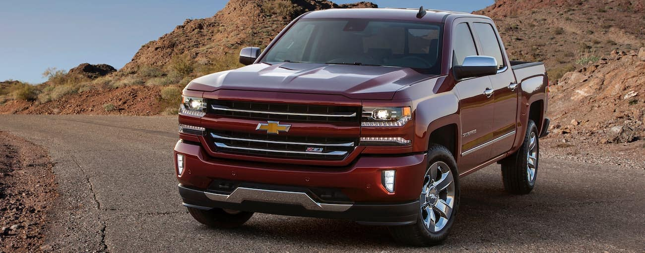 A red 2017 Used Chevrolet Silverado 1500 is parked on a road in front of desert rocks.