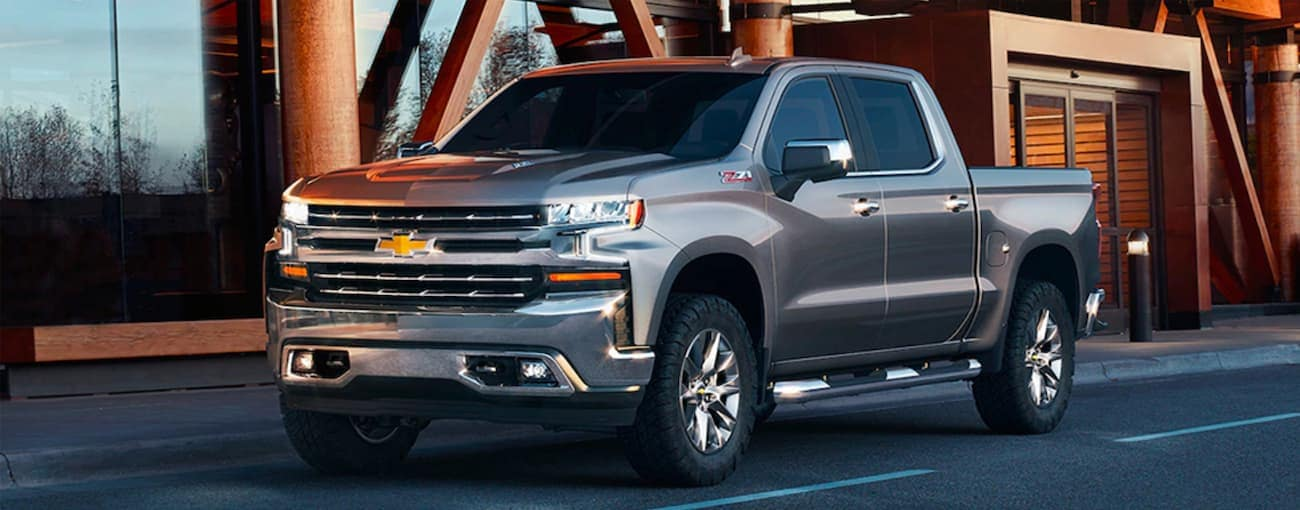 A grey 2019 Used Chevrolet Silverado 1500 is parked in front of a glass and wood building near Indianapolis, IN.