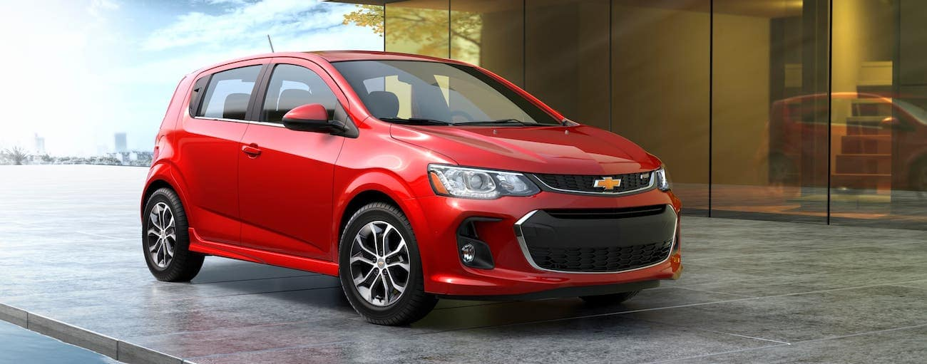 A red 2018 used Chevrolet Sonic Hatchback is parked in front of a modern home in Indianapolis, IN.