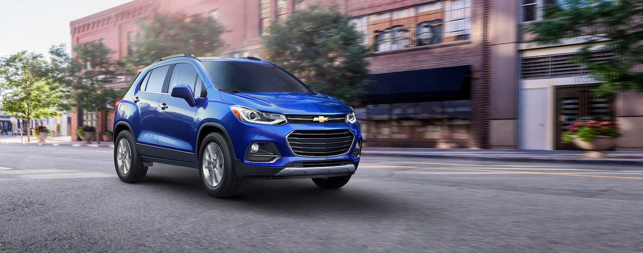A blue 2017 used Chevrolet Trax is driving on an Indianapolis, IN, street.