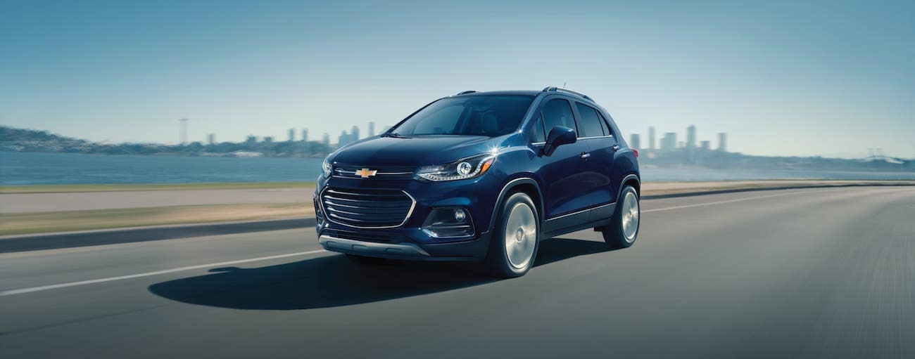 A dark blue 2018 used Chevrolet Trax is driving away from a city.