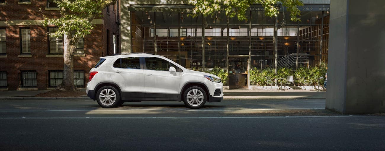 A white 2019 used Chevrolet Trax is parked in front of a cafe.