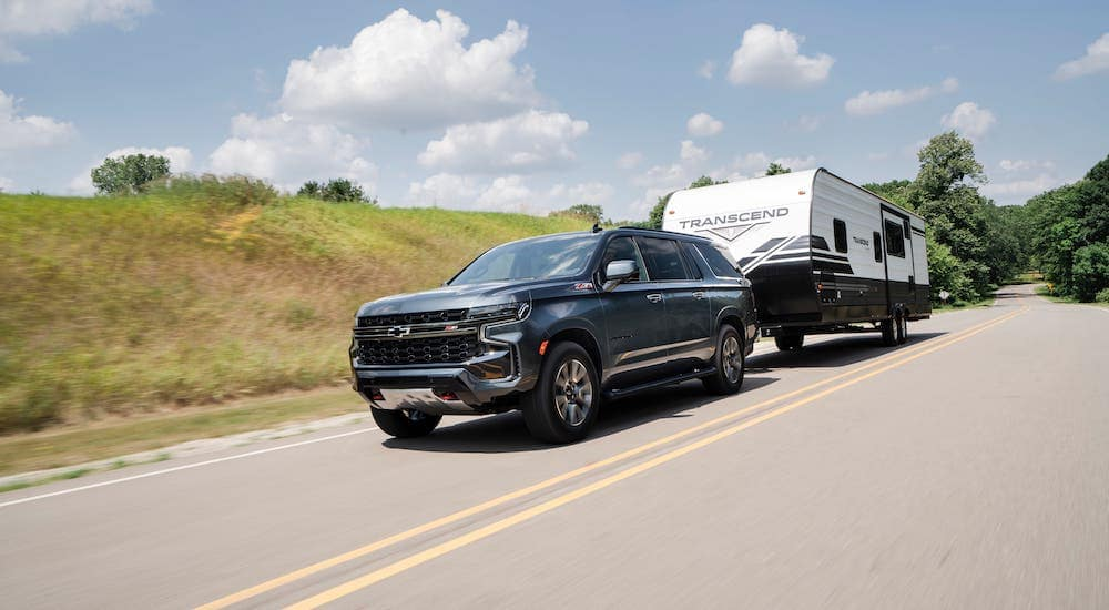 A newer Chevy SUV, a gray 2021 Chevy Suburban Z71, is towing a trailer on a highway near Indianapolis, IN.