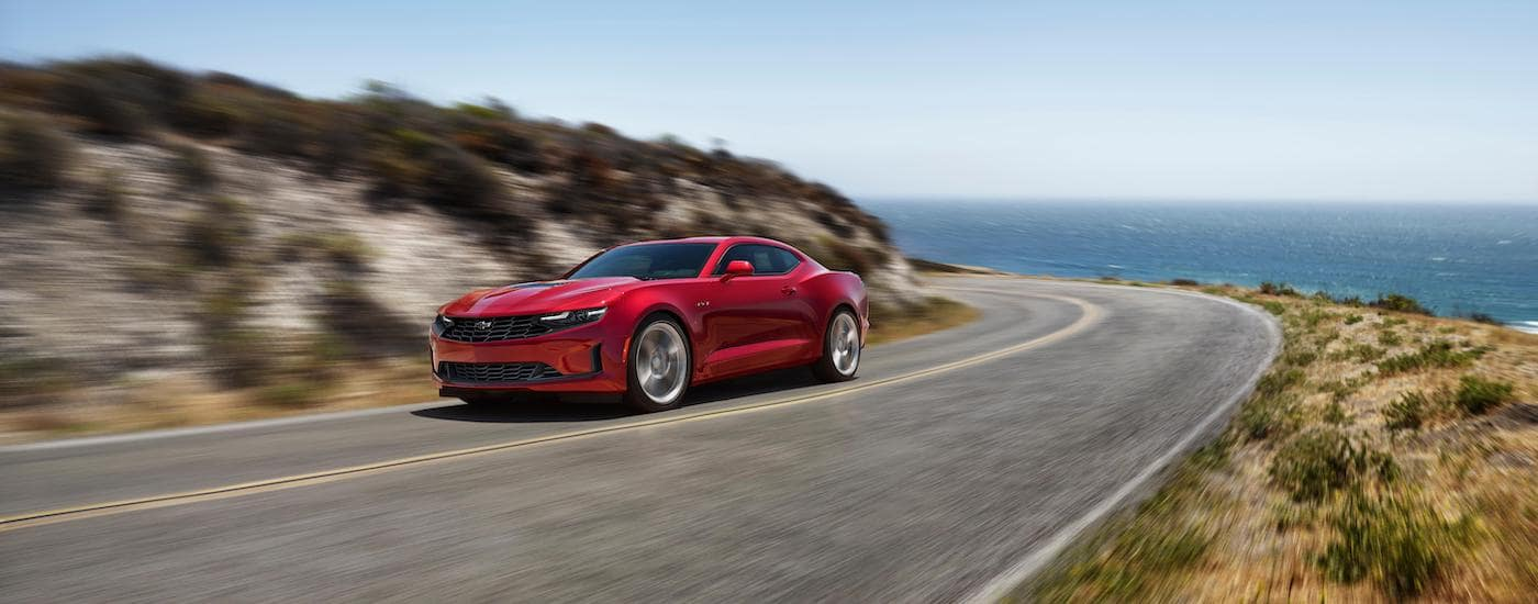 A red 2020 Chevy Camaro LT1 is driving on a coastal highway.
