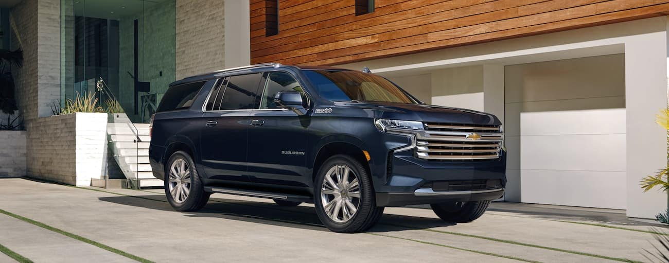 A dark blue 2021 Chevy Suburban is parked outside a modern home in Indianapolis, IN.