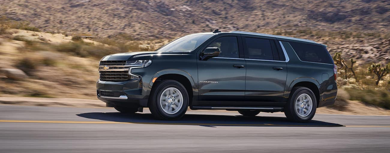 A grey 2021 Chevy Suburban is driving past desert hills.