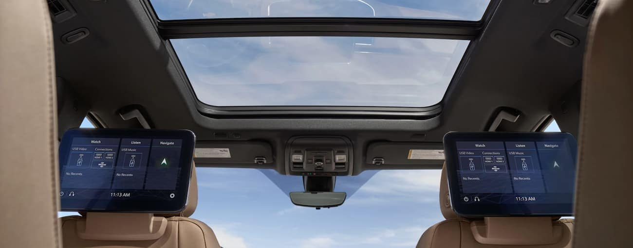 The sun roof and rear-seat infotainment screens are shown from the interior of a 2021 Chevy Suburban.