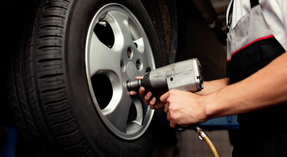 A closeup shows a mechanic's hands and an impact wrench putting a wheel on a car at a tire shop near you in Indianapolis, IN.
