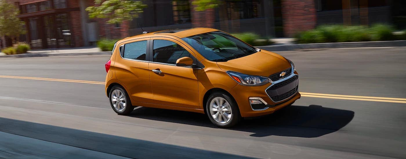 An orange 2021 Chevy Spark is driving on a street in Indianapolis, IN.