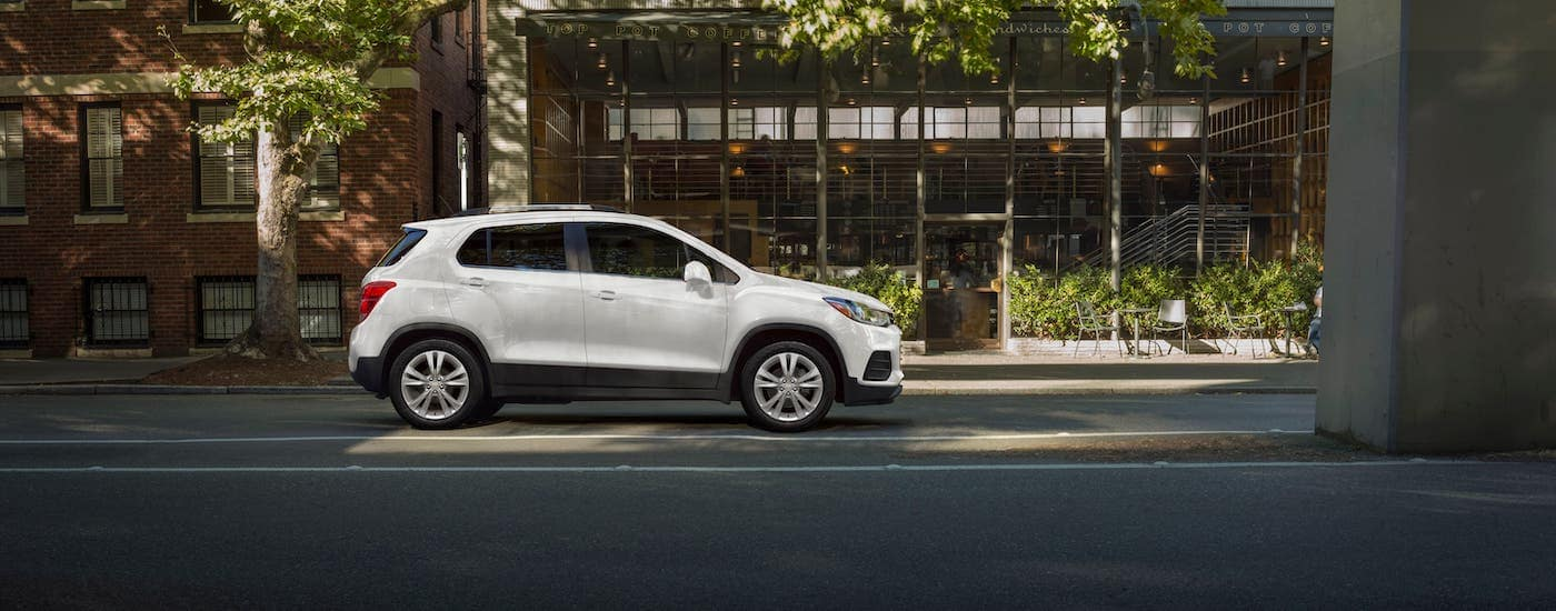 A white 2021 Chevy Trax is shown from the side while parked in front of a cafe.