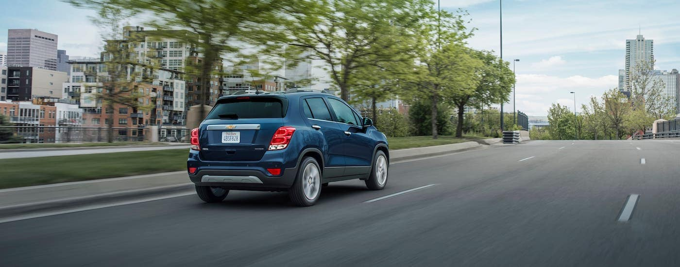 A blue 2021 Chevy Trax Premier is driving away on a highway near Indianapolis, IN.