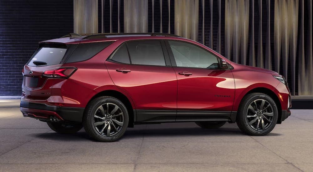 A red 2022 Chevy Equinox from a Chevy Dealer near Lawrence, Indiana, is parked in front of a stylish wall and shown from the side.