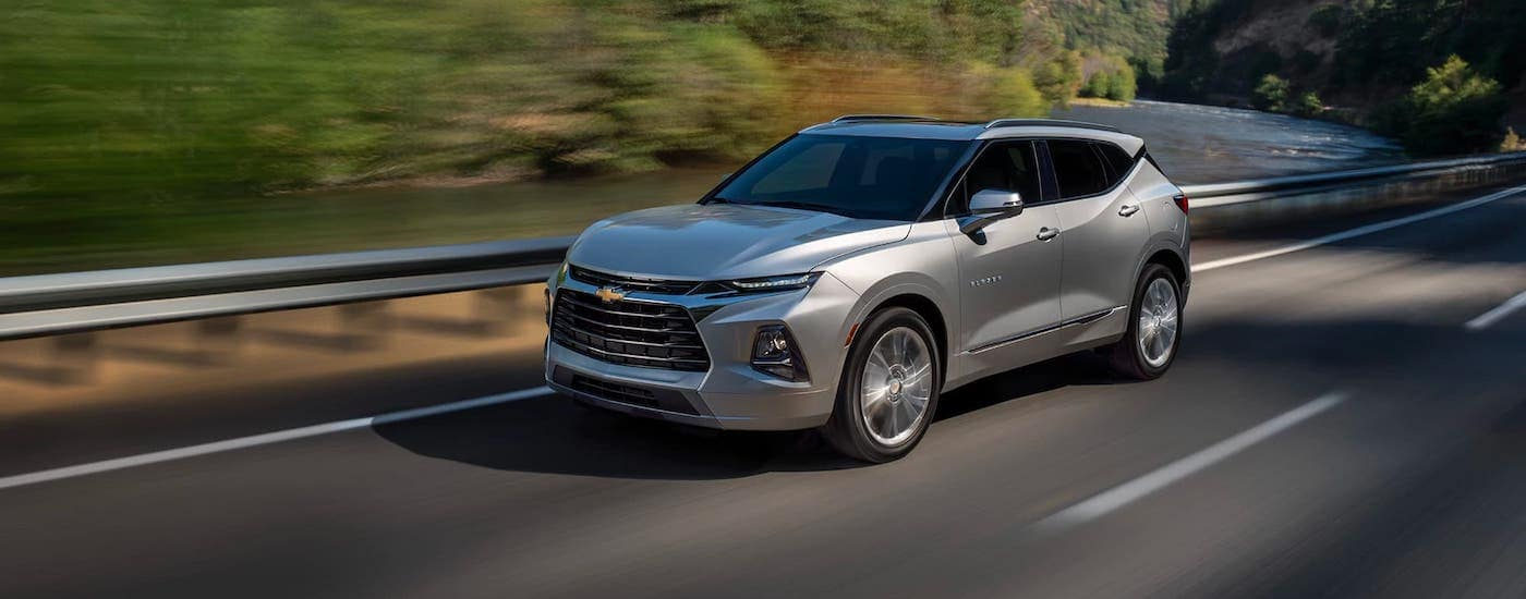 A silver 2021 Chevy Blazer is driving on an empty highway.