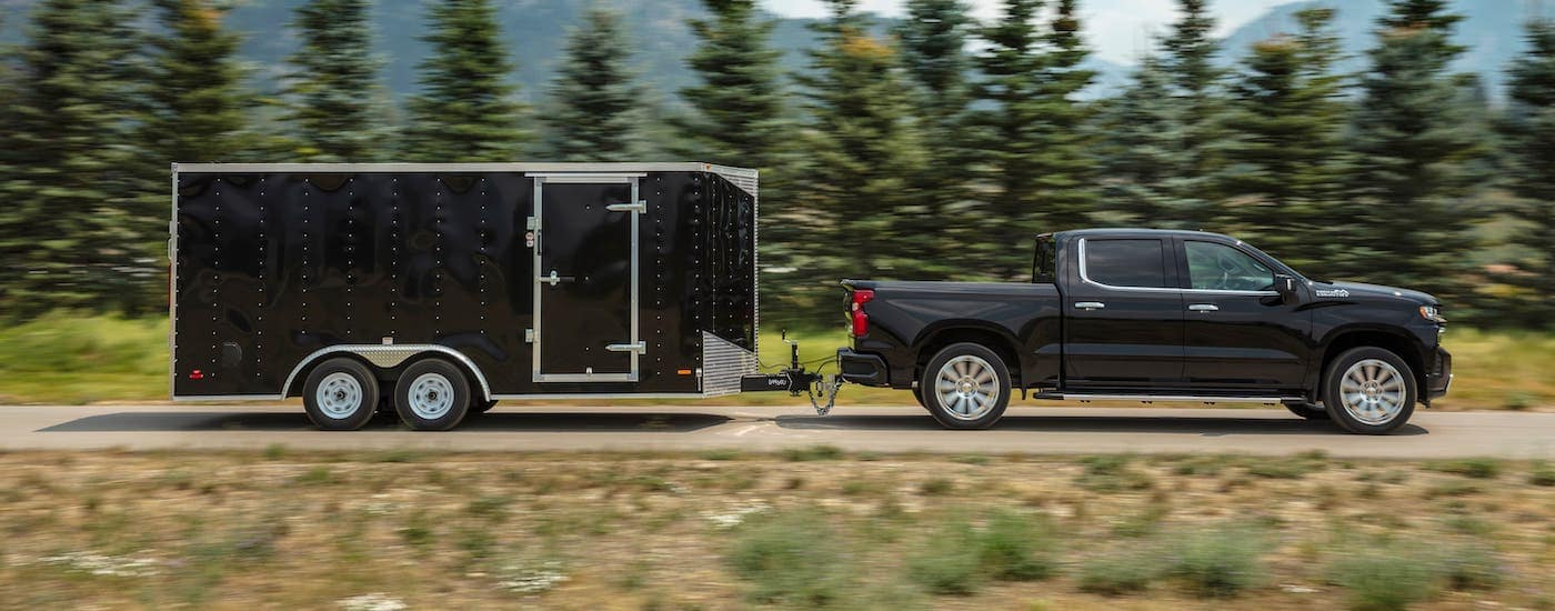 A black 2021 Chevy Silverado 1500 High Country is shown from the side while towing a black enclosed trailer.