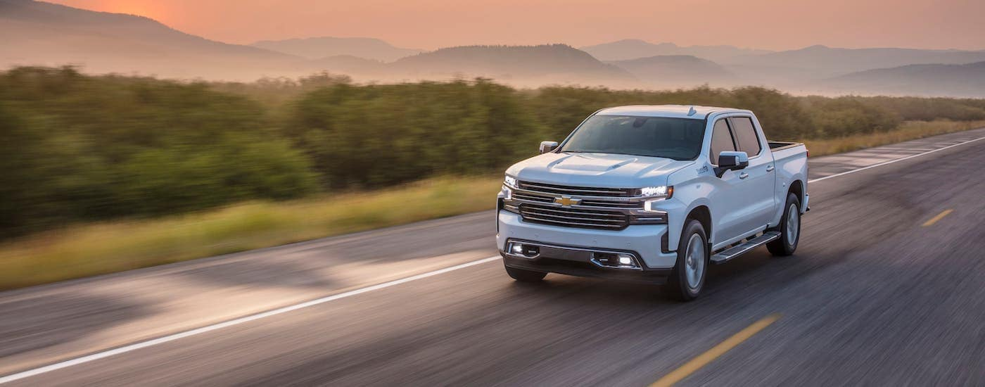 A white 2021 Chevy Silverado 1500 High Country is driving on an empty highway below a vibrant pink sunset.