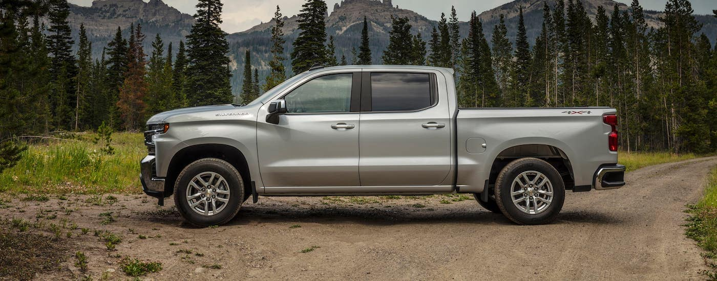 A silver 2021 Chevy Silverado 1500 LT is shown from the side while parked in front of evergreen trees and mountains.