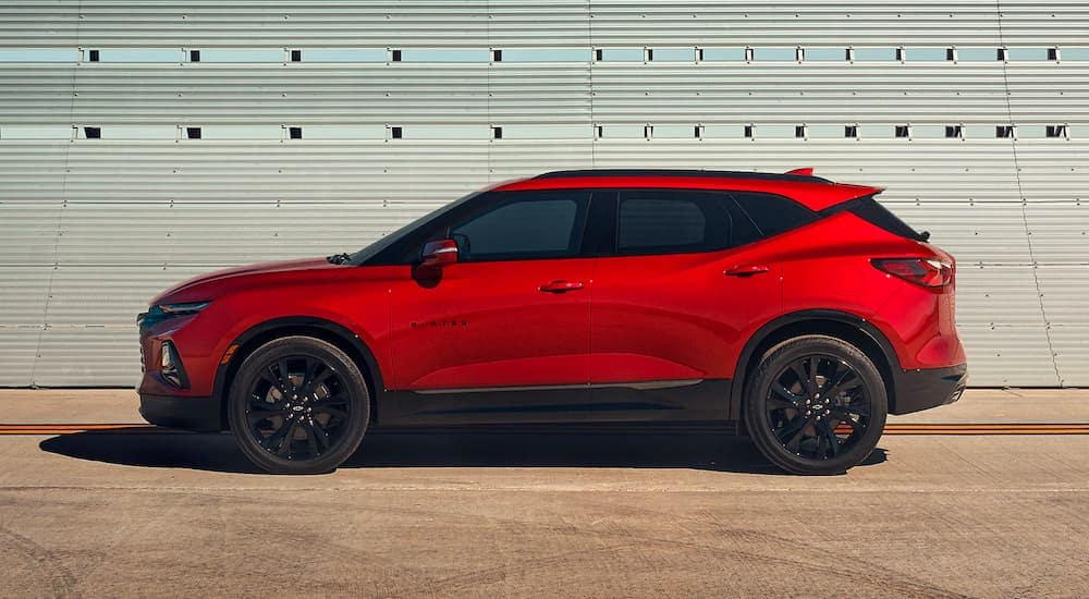 A red 2021 Chevy Blazer RS is parked in front of a metal wall after visiting a Chevy dealer near you.