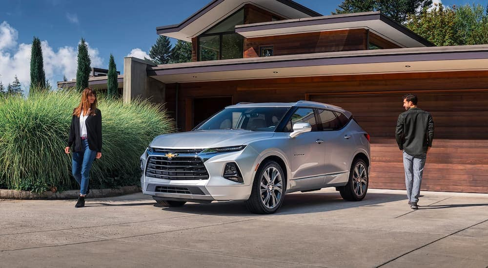 A silver 2021 Chevy Blazer is flanked by a man and woman parked in front of a modern house.