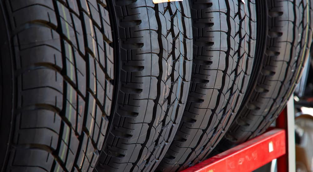 Multiple tires are shown on a metal tire rack at a tire shop near you.