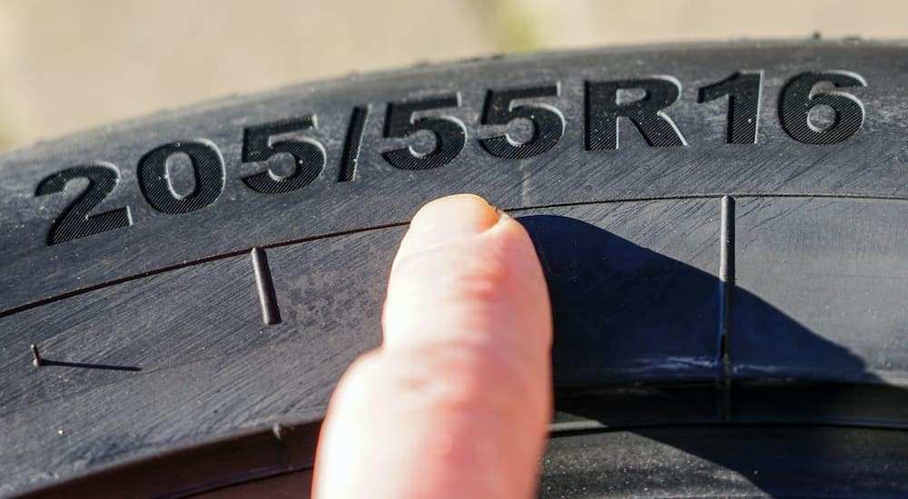A finger is pointing to the tire size designation of a wheel.