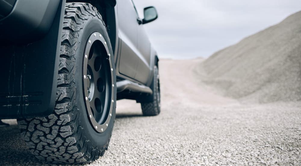 A close up is shown of the dusty tread on a truck wheel.