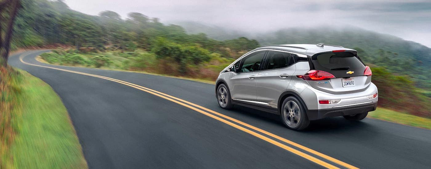 A silver 2021 Chevy Bolt EV is driving on a misty mountain road.