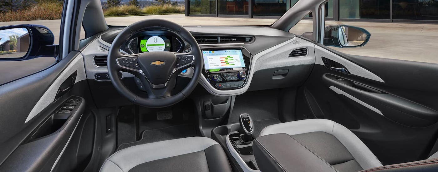 The black and gray interior of a 2021 Chevy Bolt EV is shown from the driver's perspective.