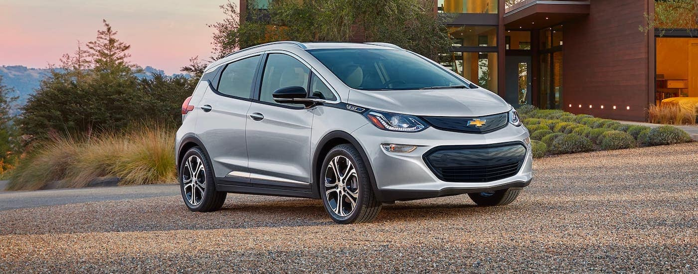 A silver 2021 Chevy Bolt EV is parked in front of a modern home at dusk.