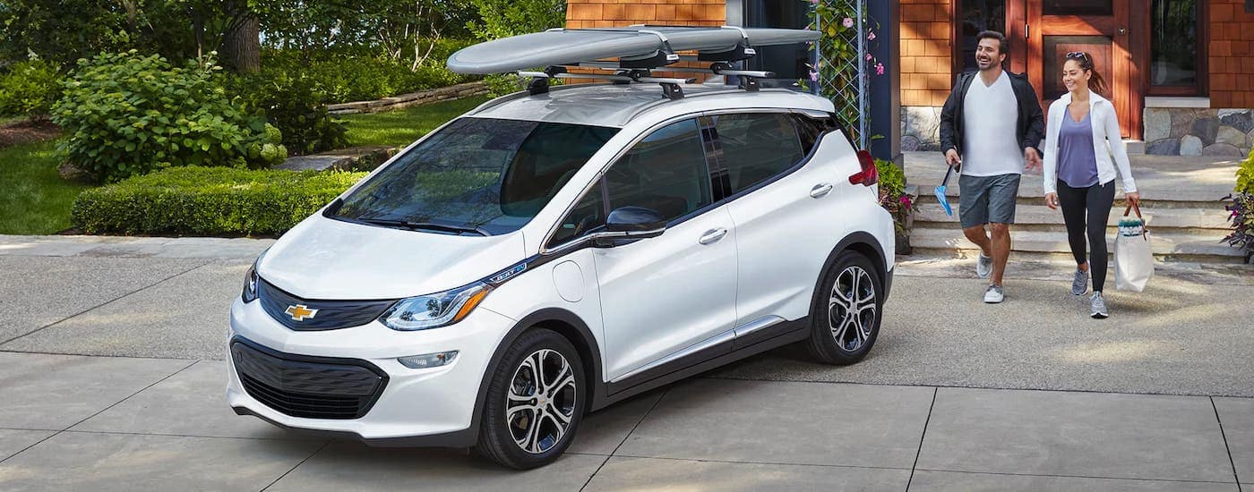 A couple is walking towards a white 2021 Chevy Bolt EV with a surfboard on the roof.