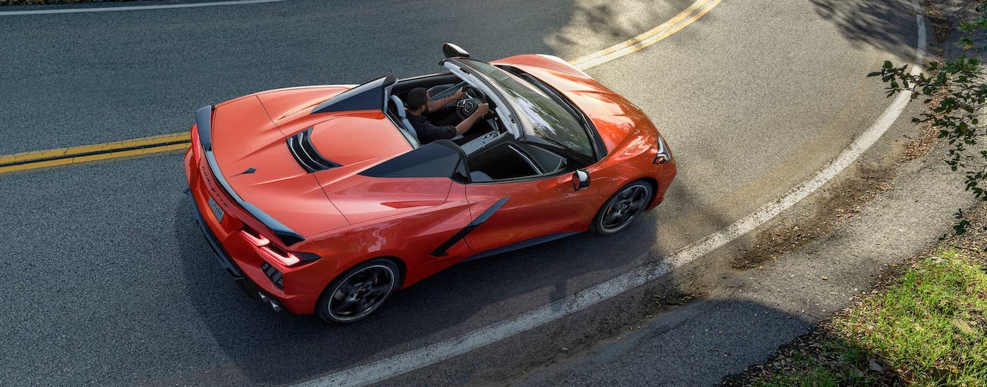 A dark orange 2021 Chevy Corvette convertible is shown from above driving on a highway.