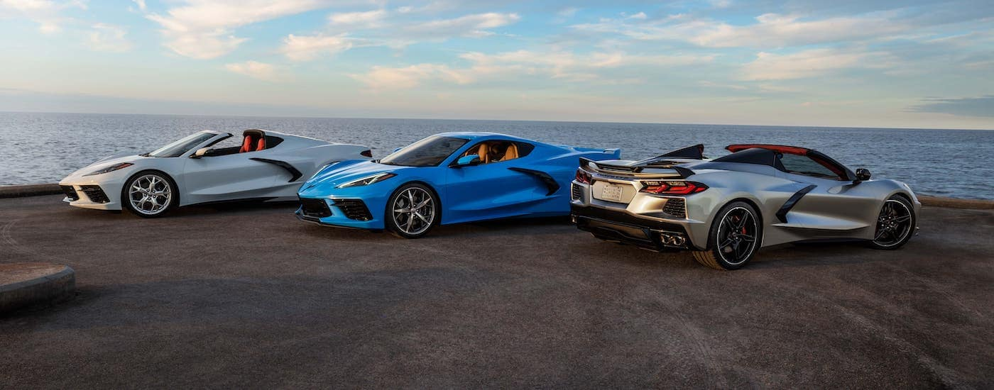 A white 2021 Chevy Corvette convertible, a blue coupe, and a silver convertible 2021 Chevy Corvette are parked in front of an ocean.