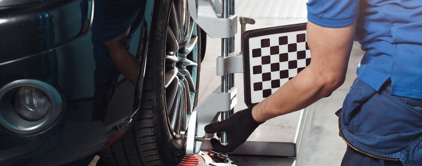 A mechanic at an autobody repair shop near you is give a car a tire alignment.