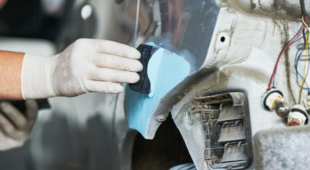 A close up is shown of a mechanic using body filler on a grey car.