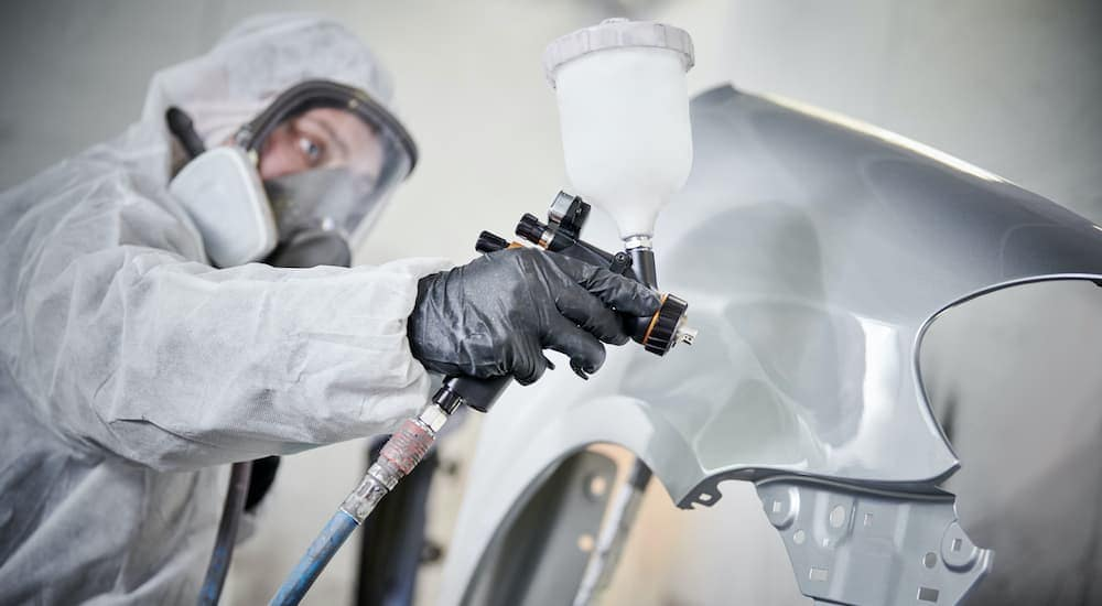 A close up is shown of a technician spraying paint on a silver fender.