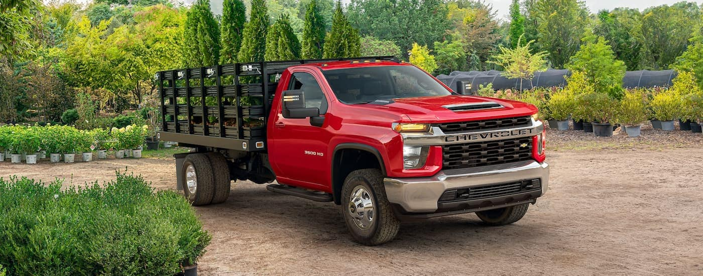 A red 2021 Chevy 3500 HD is driving past potted plants with plants in the gated bed.