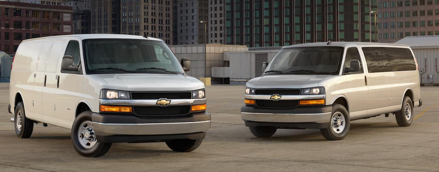 Two Chevy commercial vehicles, both off-white 2021 Chevy Express Vans, are parked in front of city buildings.