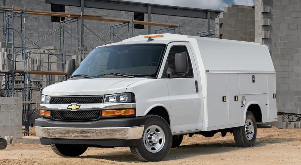 A white 2021 Chevy Express Cutaway with a Utility Upfit is at a construction site.