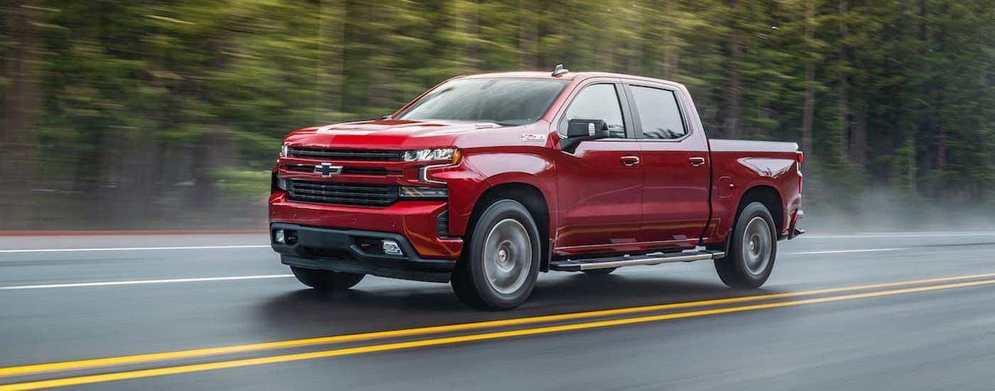 A red 2021 Chevy Silverado 1500 is driving on a wet road past pine trees.