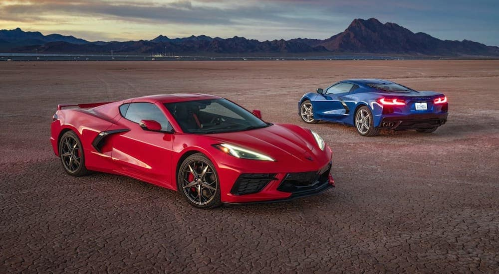 A red and a blue 2021 Chevy Corvette Stingray are parked on an empty flat in front of mountains.