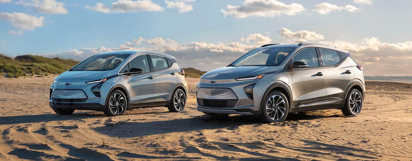 A light blue 2022 Chevy Bolt EV is parked next to a silver 2022 Chevy Bolt EUV at the beach.