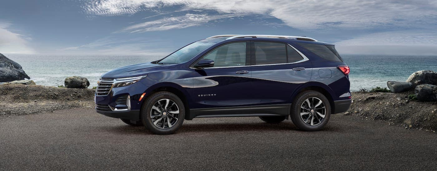 A blue 2022 Chevy Equinox Premier is shown from the side parked in front of an ocean.