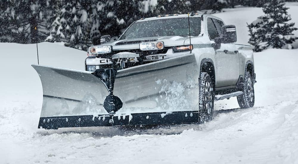 A white 2021 Chevy Silverado 2500 HD with a plow is in a snow storm.