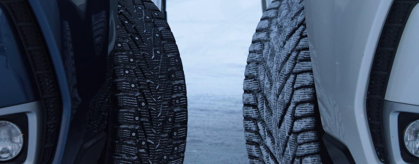 A studded tire is next to a snow tire without studs.